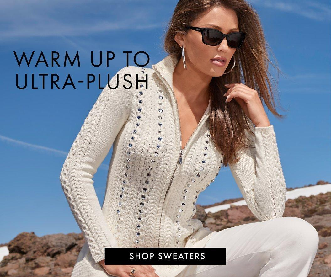 model wearing a jewel studded beige zip-up cable knit sweater, white jeans, sunglasses, and silver hoop earrings. left text: warm up to ultra-plush.
