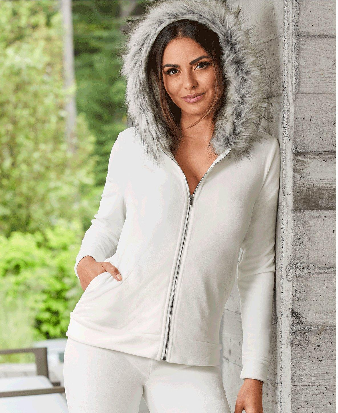 model wearing a white warm up with a faux-fur lined hood.