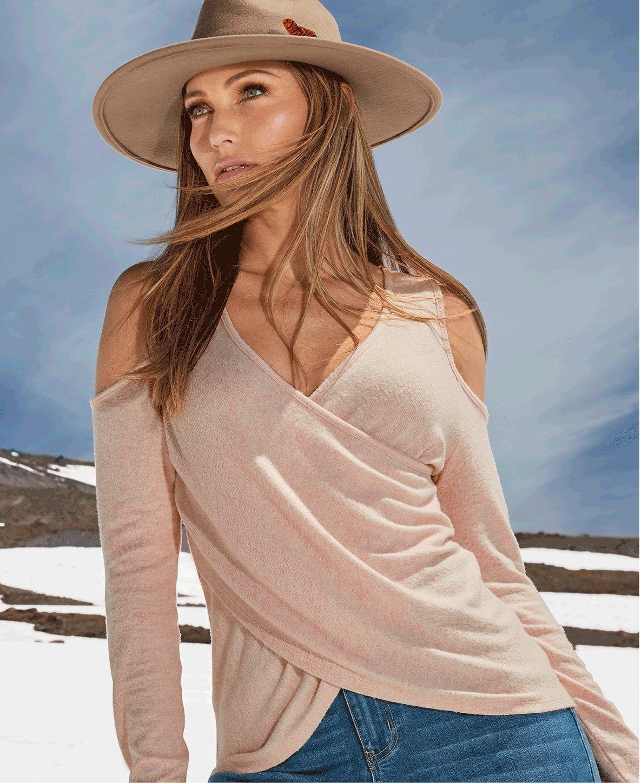 model wearing a light pink surplice long-sleeve cold-shoulder top, jeans, and beige hat.