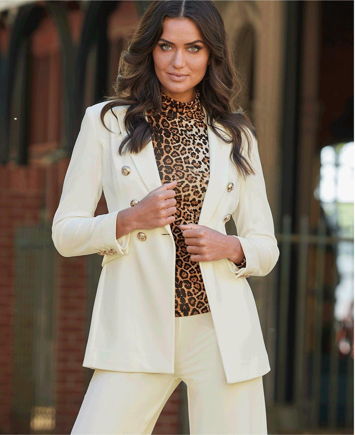model wearing a white double-breasted blazer, leopard print turtleneck top, and white pants.