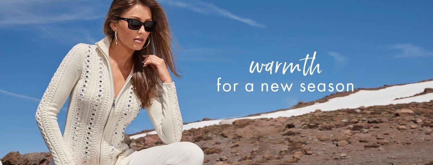 model wearing a jewel studded beige zip-up cable knit sweater, white jeans, sunglasses, and silver hoop earrings. text: warmth for a new season.