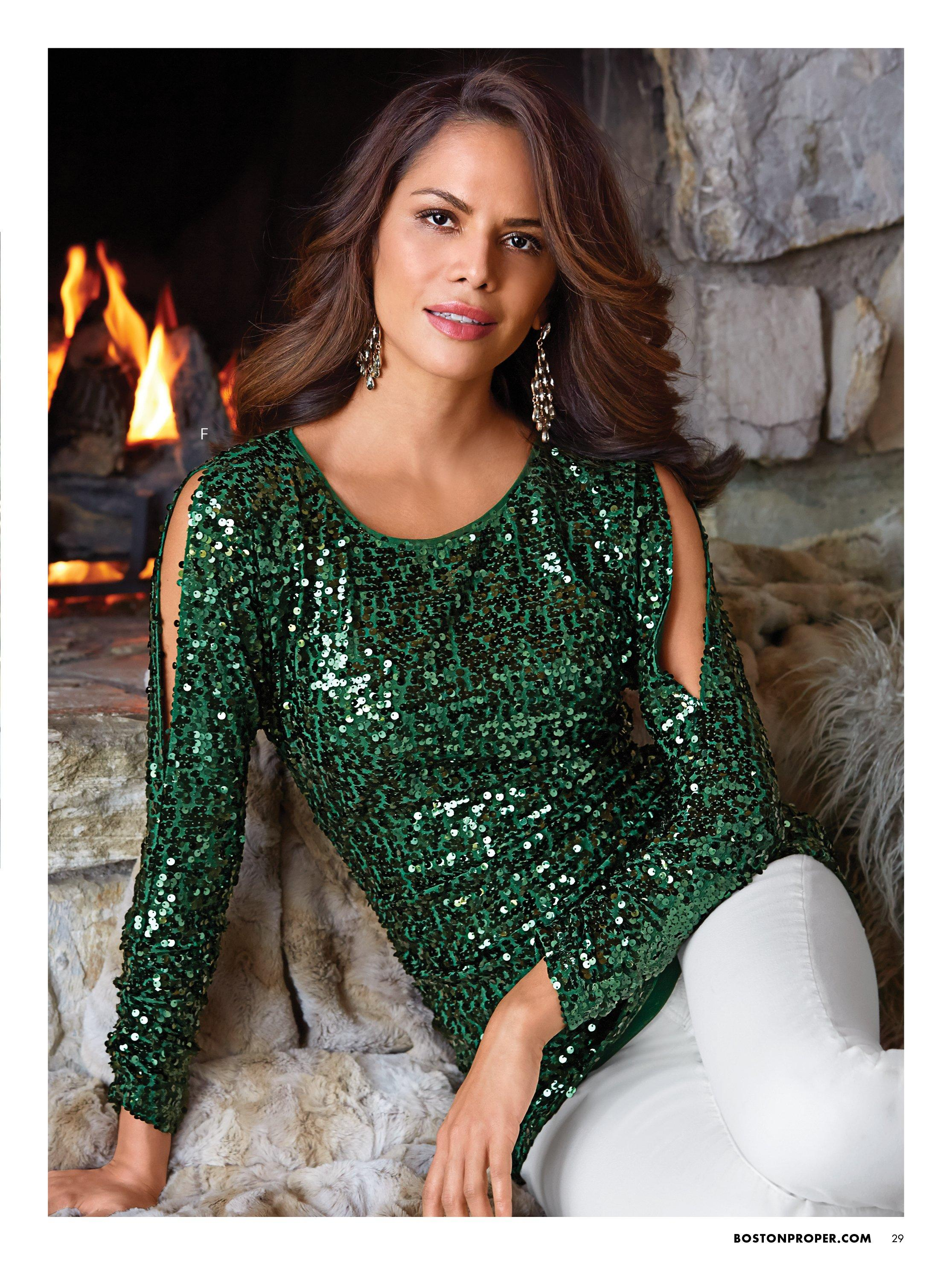 model wearing a green long sleeve cold shoulder sequin top and white jeans.