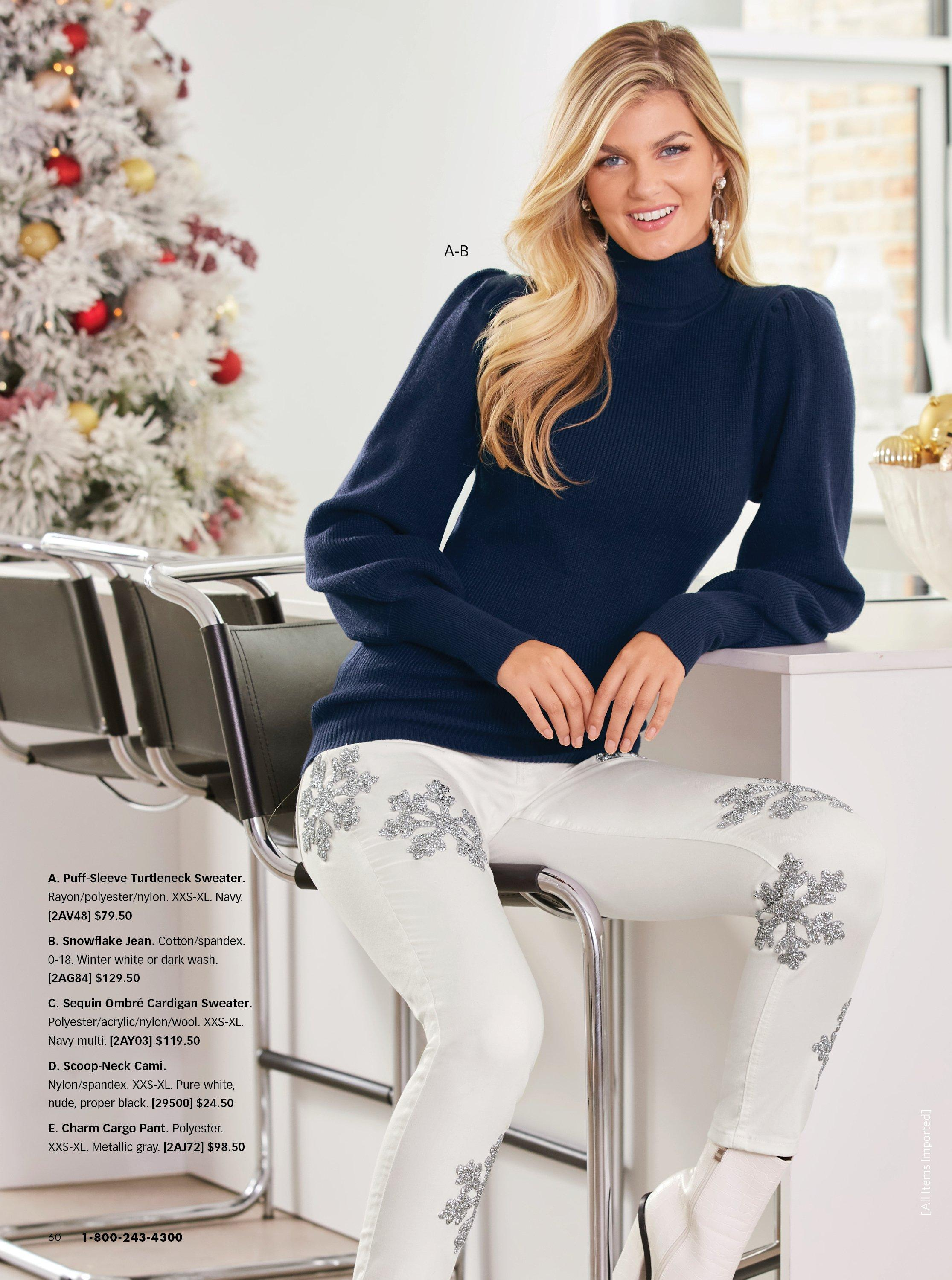 model wearing a navy turtleneck balloon sleeve sweater, white snowflake embellished jeans, and white boots.