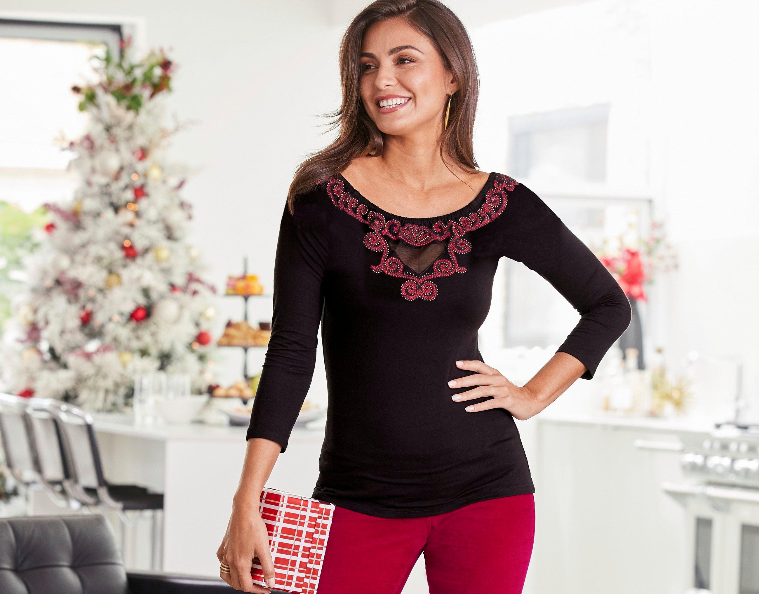 model wearing a black and red embroidered sweater and red velvet pants.