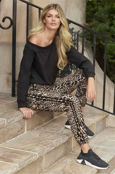 model wearing a black slouchy sweatshirt, animal print joggers, and black sneakers.