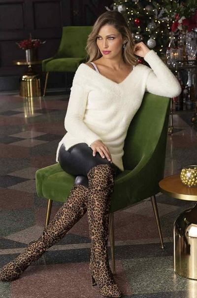 model wearing a white plush v-neck sweater, rhinestone embellished bra straps, black faux-leather leggings, and leopard print over-the-knee boots.