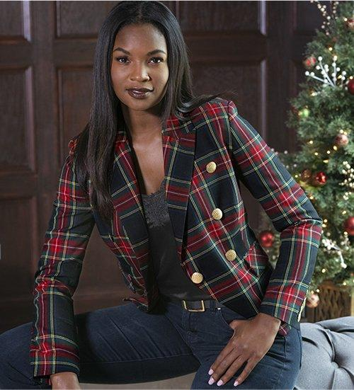 model wearing a red and green plaid blazer, black lace tank top, and jeans.