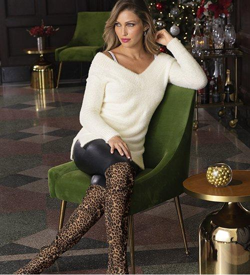 model wearing a white plush v-neck sweater, rhinestone studded bra straps, black faux leather leggings, and over-the-knee leopard print boots.