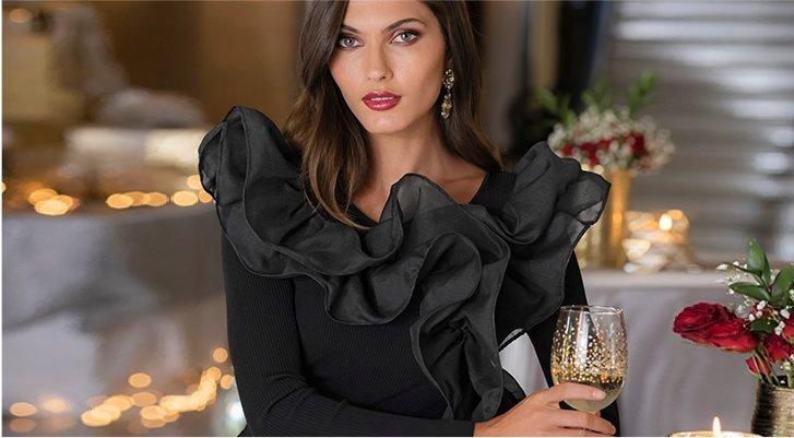 model wearing a black organza sweater with ruffles.
