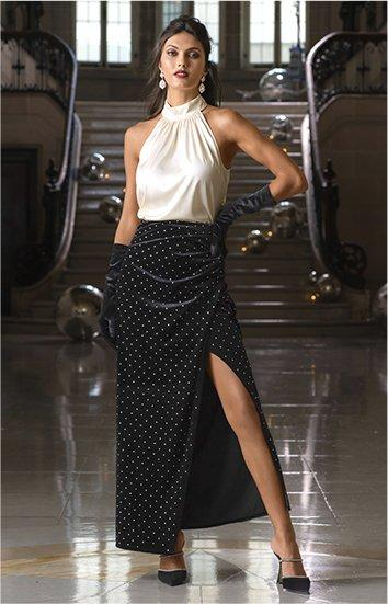 model wearing a white mock-neck sleeveless top, black silver studded maxi skirt, black gloves, and black heeled mule shoes.