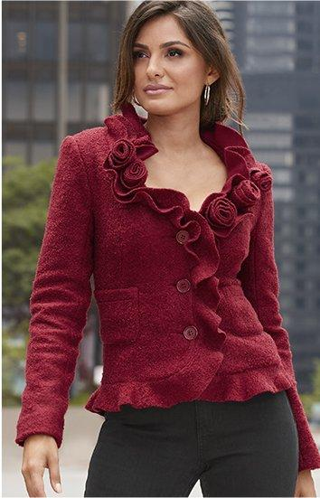 model wearing a red ruffle and rosette cardigan and black pants.