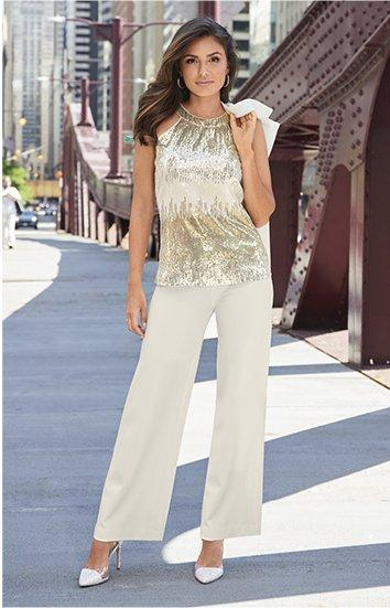 model wearing a silver and gold sequin sleeveless top, off-white palazzo pants, and silver rhinestone heels.