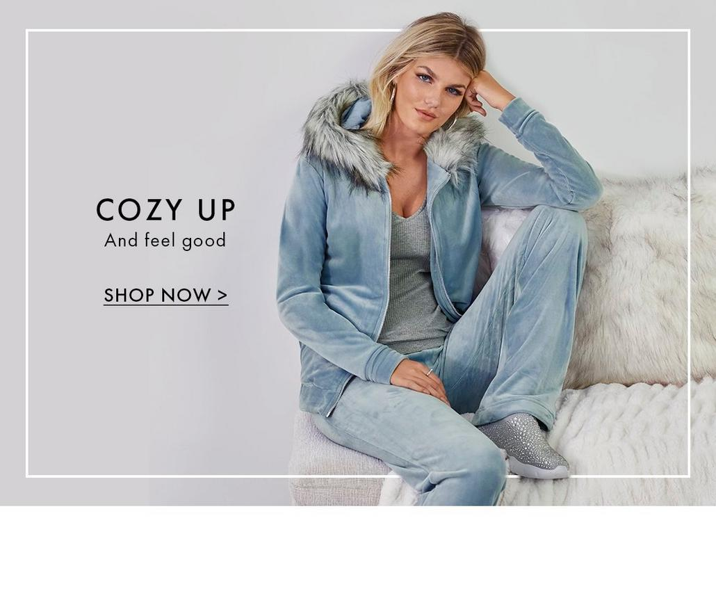 model wearing a light blue velour faux fur two-piece warm-up set and gray tank top. text: cozy up and feel good. shop now.