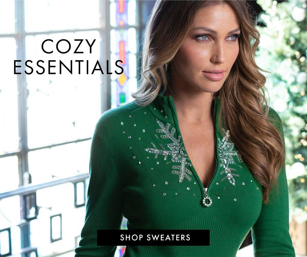 model wearing a green snowflake embellished half zip sweater. text: cozy essentials. shop sweaters.