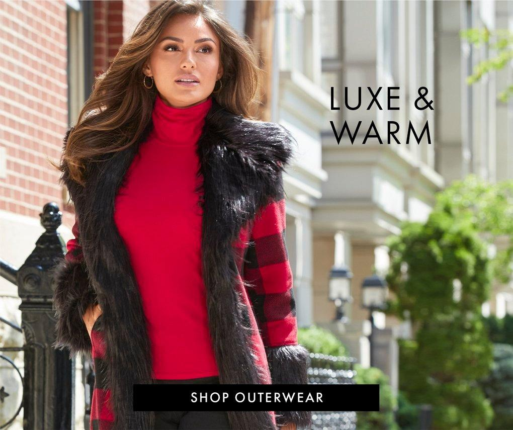 model wearing a red and black plaid faux fur coat, red turtleneck top, and black pants. text: luxe & warm. shop outerwear.