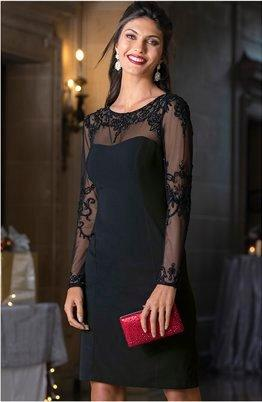 model wearing a black lace illusion long sleeve dress while holding a red clutch.