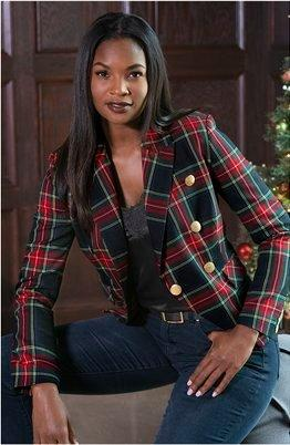 model wearing a green and red plaid blazer, black lace tank top, and jeans.