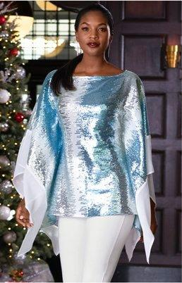 model wearing a blue sequin poncho and white pants.