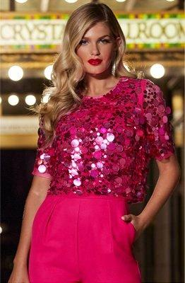 model wearing a pink short sleeve sequin embellished jumpsuit.