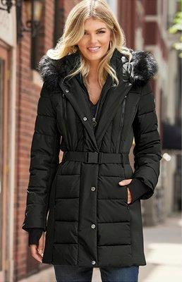 model wearing a black puffy faux-fur coat and black faux-leather leggigngs.