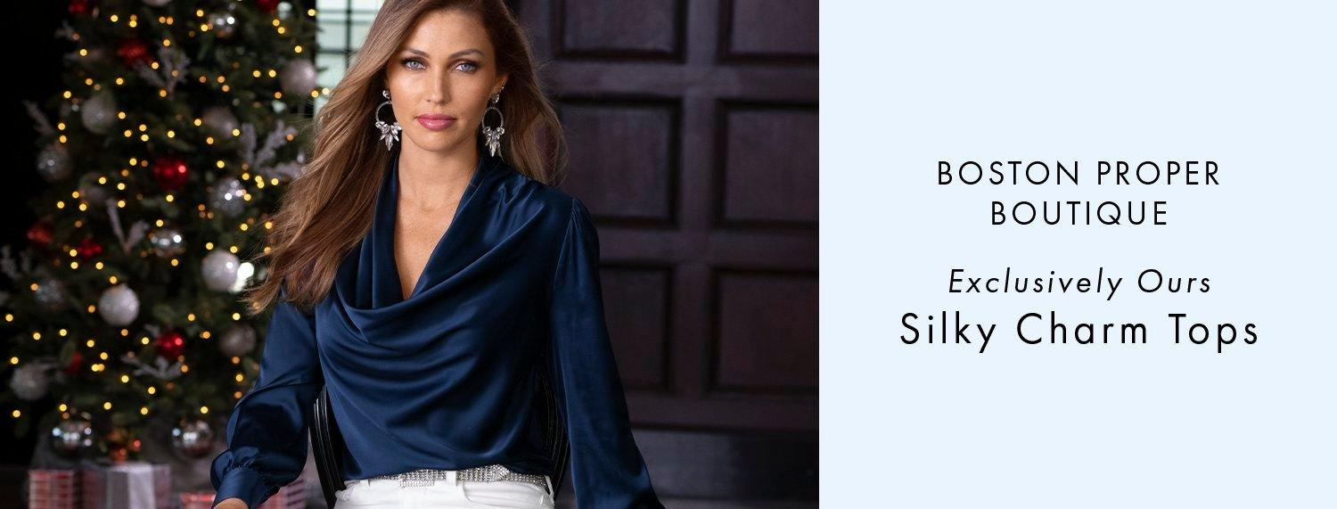 model wearing a blue long-sleeve cowl neck top, white pants, silver hoop earrings, and silver rhinestone belt. text: boston proper boutique. exclusively ours. silky charm tops.
