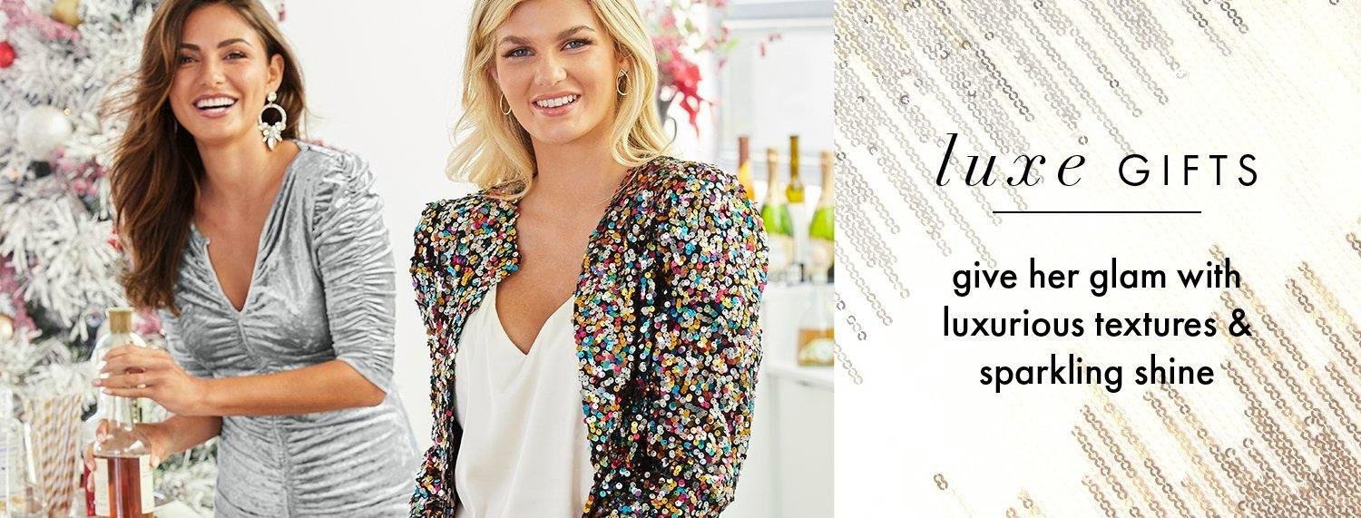 left model wearing a silver ruched long-sleeve top. right model wearing a multicolored sequin blazer and white v-neck tank top. text: luxe gifts give her glam with luxurious textures & sparkling shine.