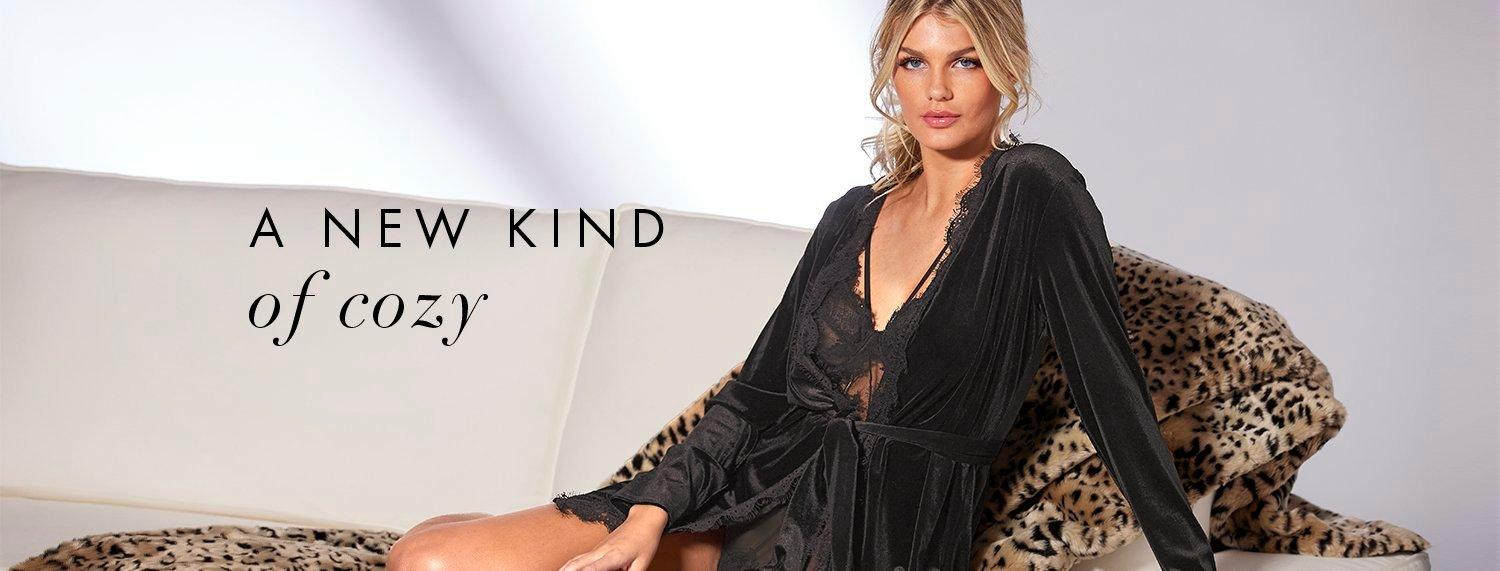 model wearing a black velour robe white laying on leopard print faux fur throw. text: a new kind of cozy.