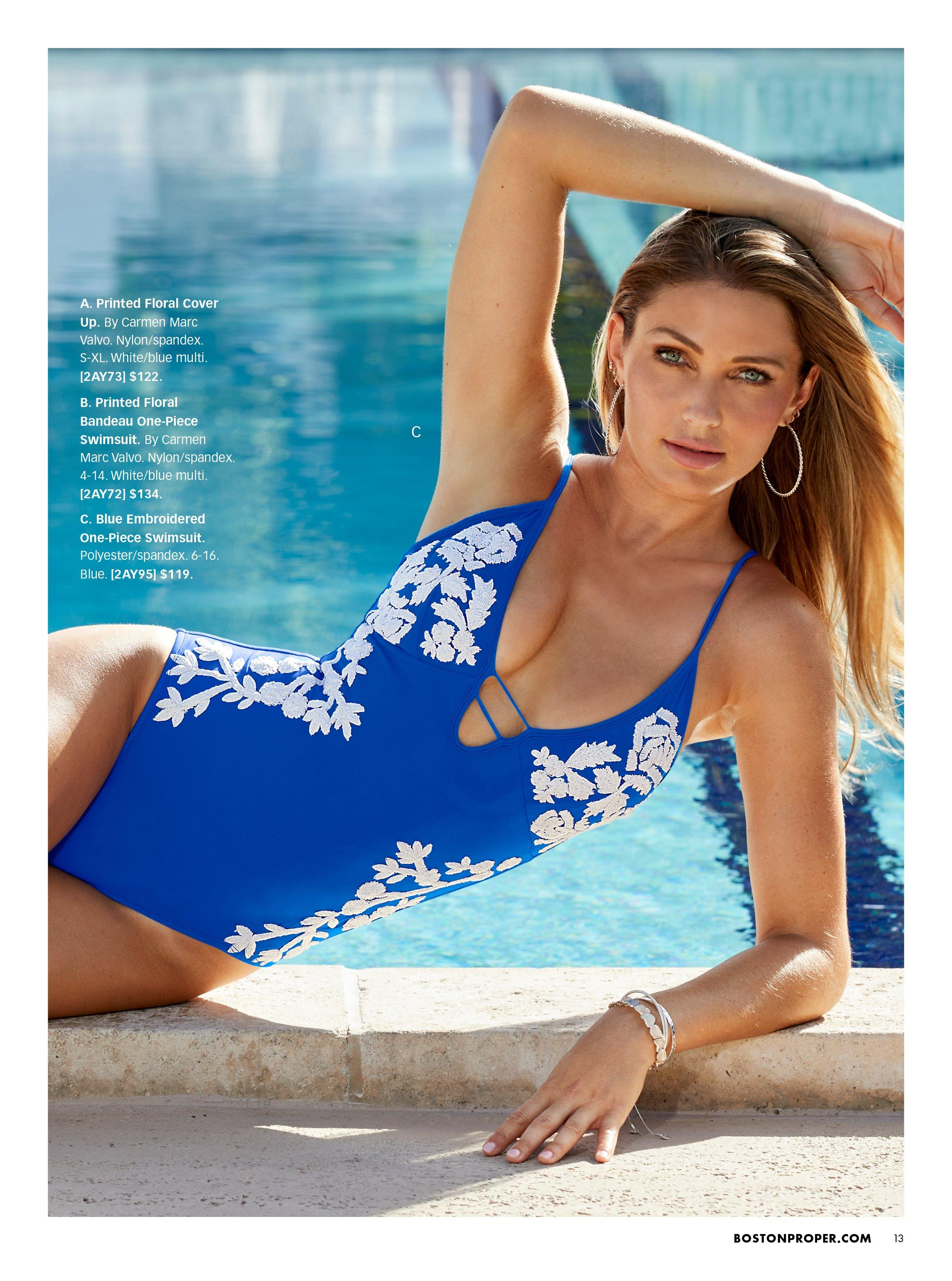 model wearing a blue one-piece swimsuit with white embroidered flowers.