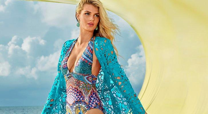 model wearing a blue lace duster and a printed halter neck deep plunge one piece swimsuit and turquoise earrings.