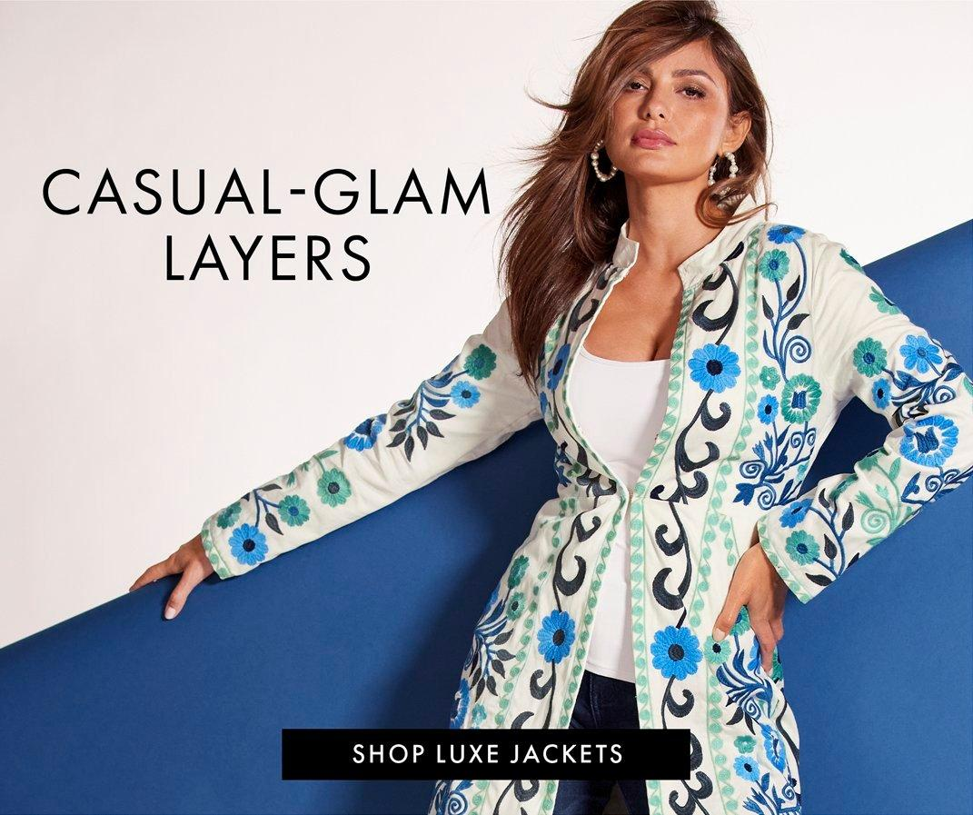 black text: casual-glam layers. shop lux jackets. model wearing a white jacket with blue floral embroidery, white tank top, jeans, and silver hoop earrings.