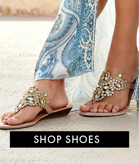 model wearing gold crystal embellished sandals.