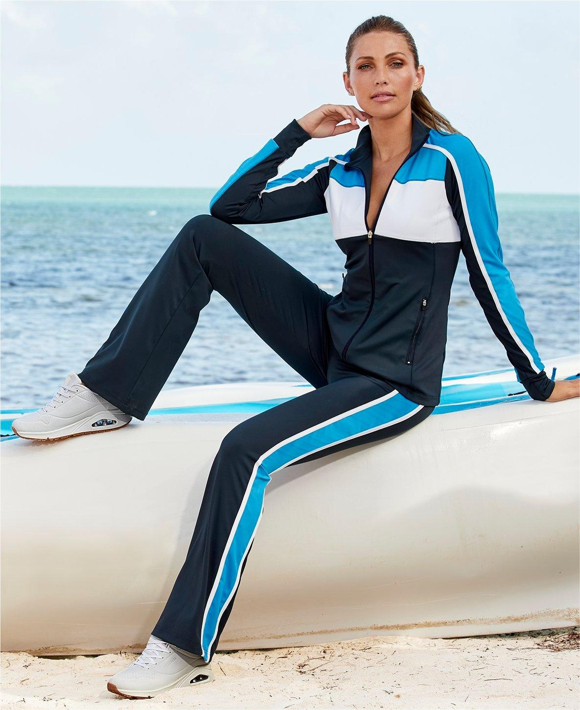 model wearing a blue and white color block two-piece sport set and white sneakers.