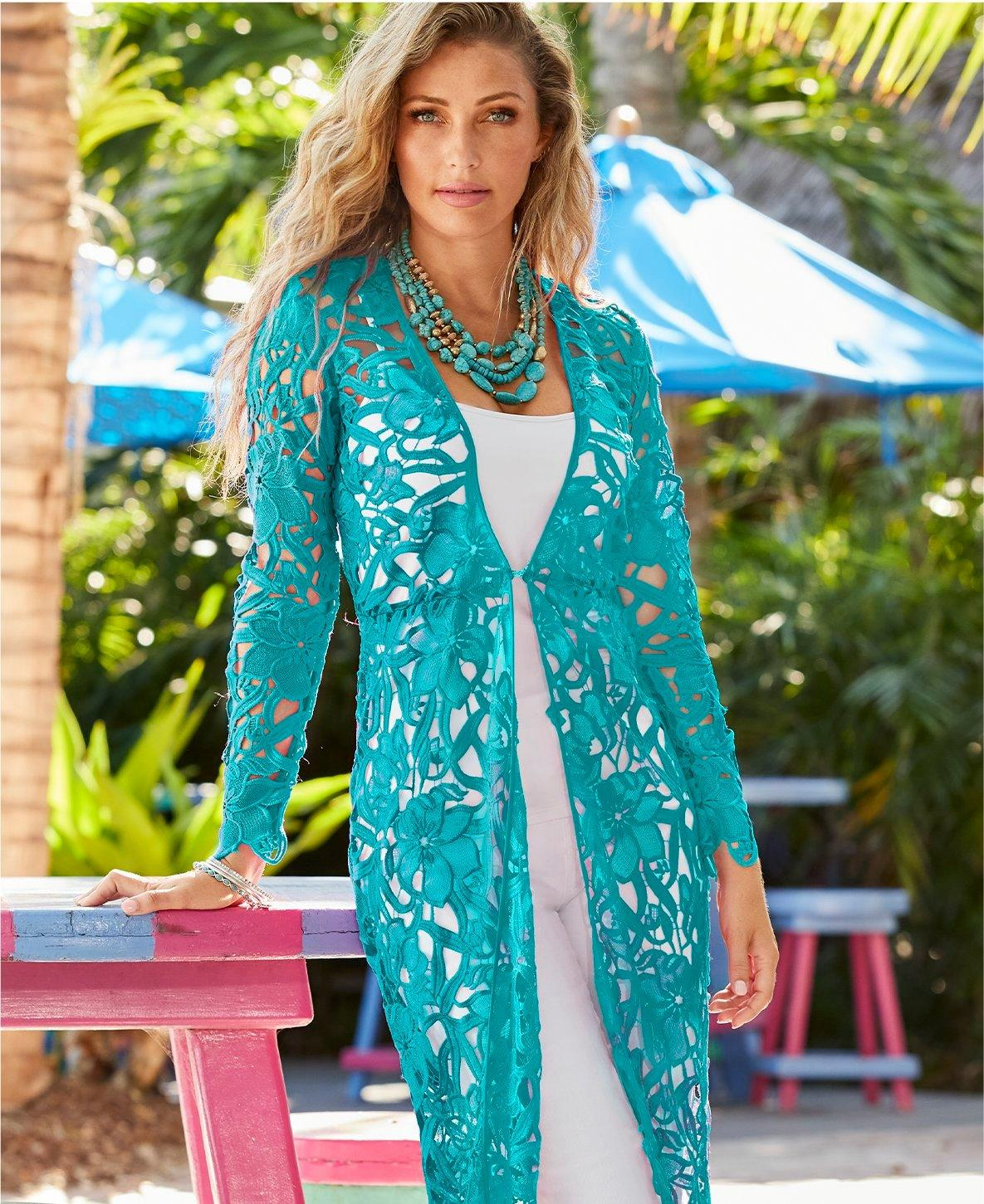 model wearing a blue lace duster, white tank top, white jeans, and a layered turquoise stone necklace.