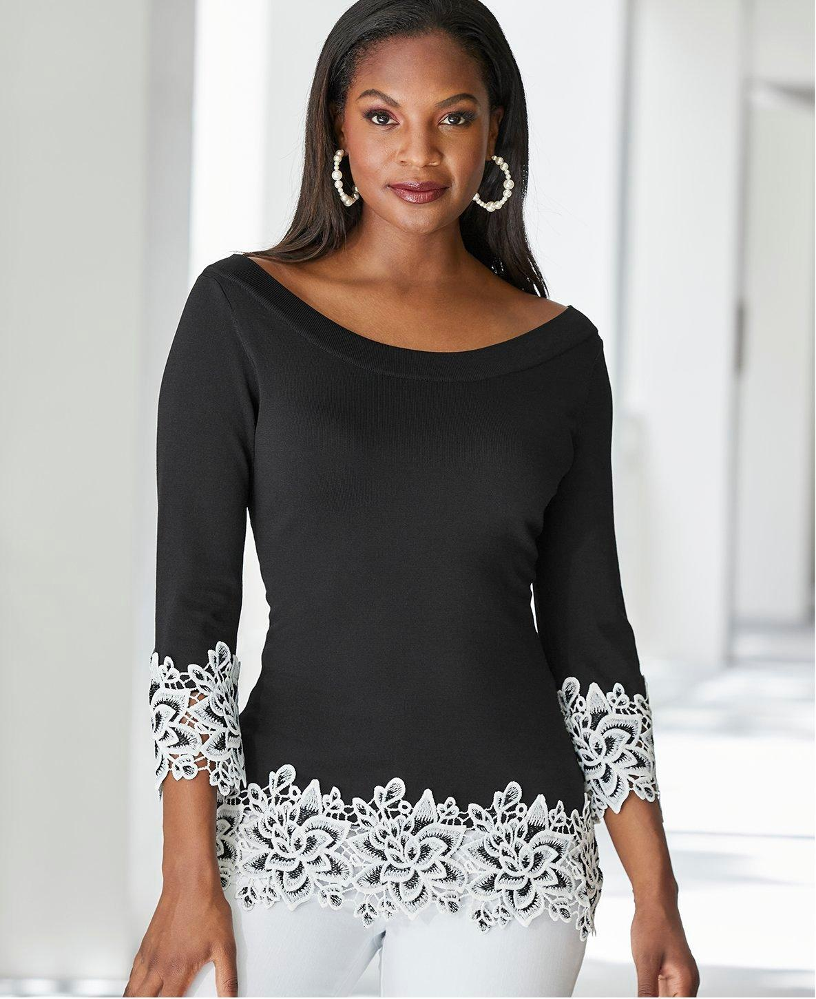 model wearing a black sweater with white lace trim, white pants, and pearl hoop earrings.