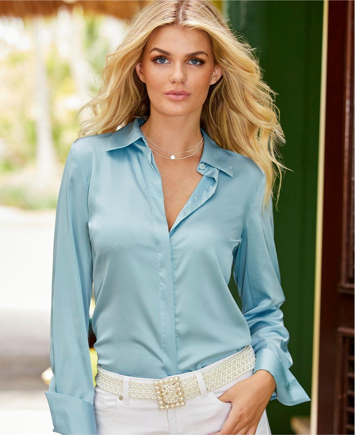 model wearing a light blue button down long-sleeve charm top, pearl belt, and white jeans.