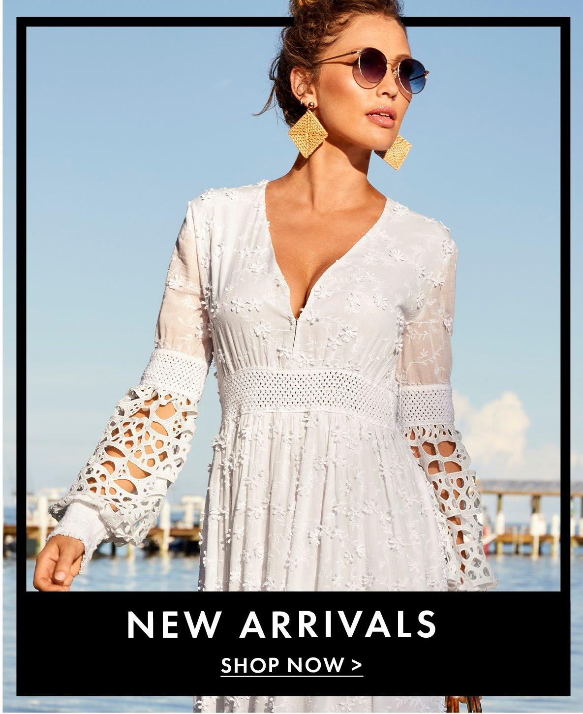 model wearing a white lace long-sleeve maxi dress, straw earrings, and sunglasses.