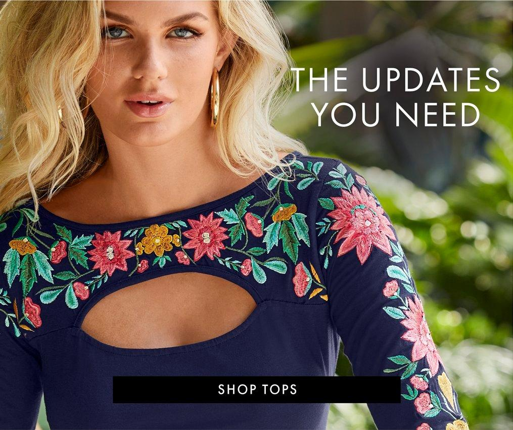 model wearing a blue cutout long-sleeve top with floral embroidery and gold hoop earrings.