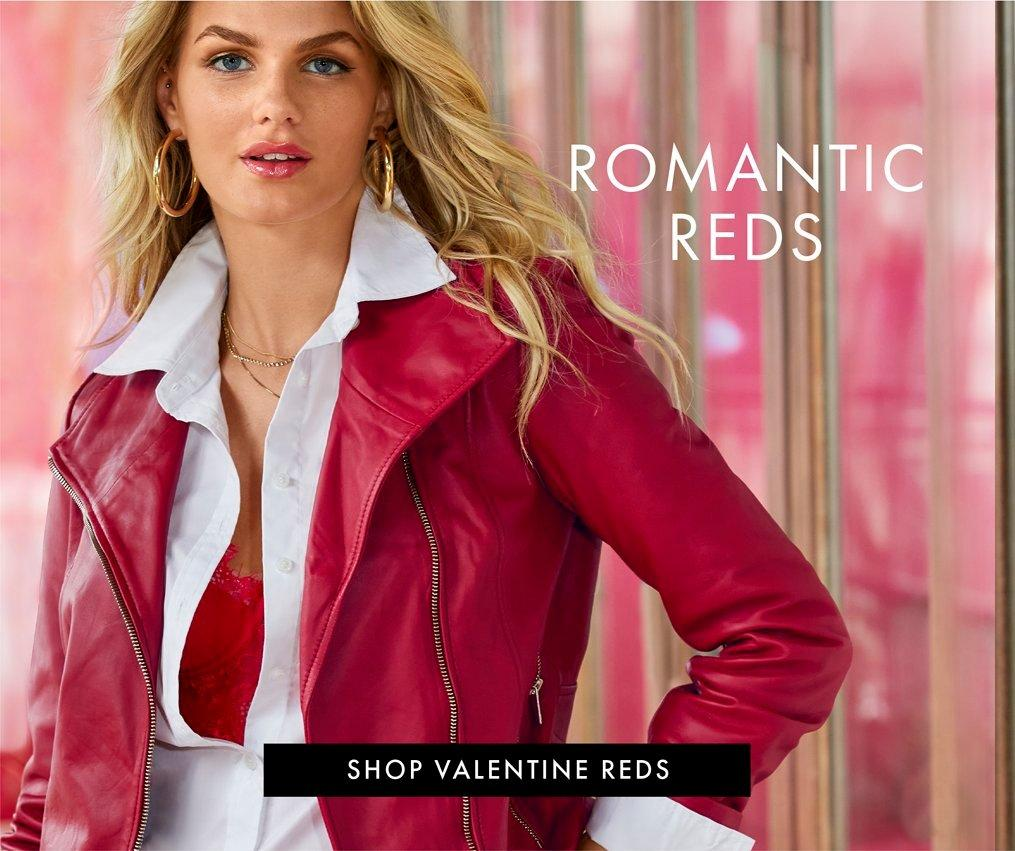 model wearing a red leather jacket, white button down shirt, red lace bodysuit, and gold hoop earrings.