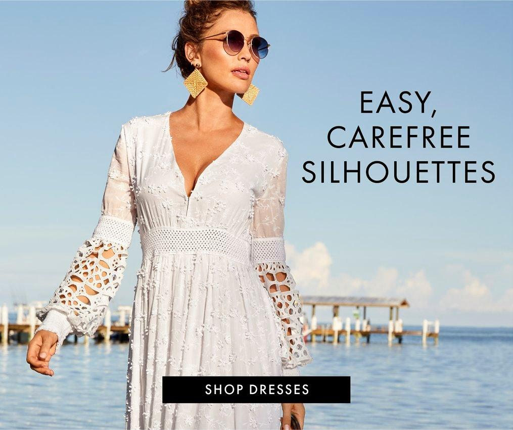 model wearing a white long-sleeve lace maxi dress, tan square earrings, and circular sunglasses.