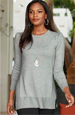 model wearing a red slouchy off-the-shoulder sweater, black beanie, and black pants.