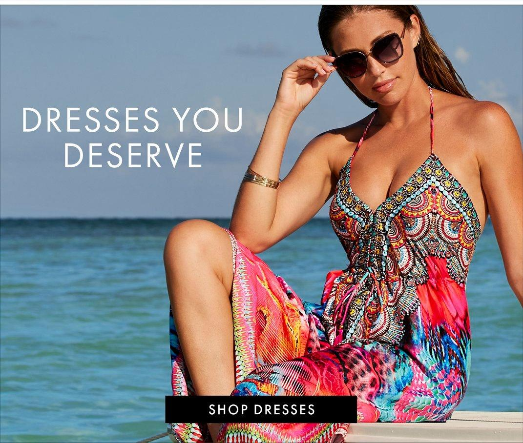 white text: dresses you deserve. shop dresses. model wearing a multicolored animal print halter maxi dress and sunglasses.