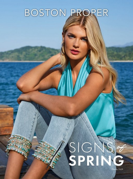 model wearing a light blue cowl neck sleeveless top, light wash jewel embellished ankle jeans, and silver hoop earrings.