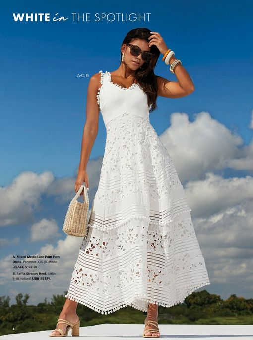 model wearing a white lace and pompom embellished maxi dress, raffia strappy heels, a pearl embellished straw bag, pearl hoop earrings, and sunglasses.