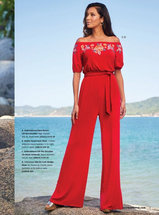 model wearing a red tie-waist off-the-shoulder jumpsuit with floral embroidery and silver strappy cork wedges.