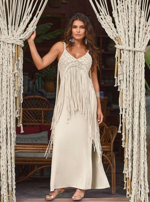 model wearing a light tan crochet fringe maxi dress and silver slip-on wedges.