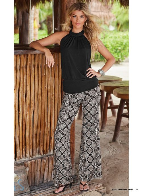 model wearing a black halter neck sleeveless top, python print palazzo pants, black low-heel thong sandals, and gold hoop earrings.