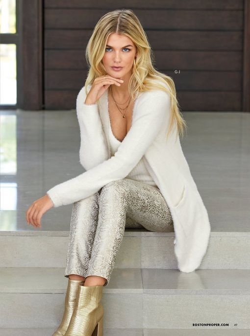 model wearing a plush white cardigan, white sweater tank top, white and gold snake foil print skinny jeans, gold hoop earrings, and gold heeled booties.