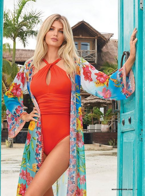 model wearing a coral one-piece keyhole halter swimsuit and a multicolored printed duster.