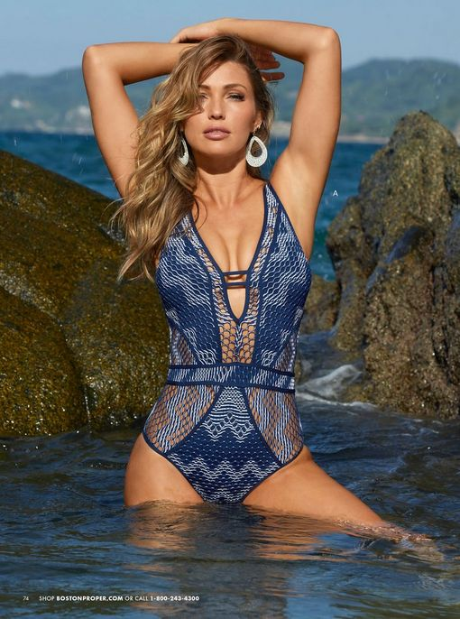 model wearing a navy crochet plunge one-piece swimsuit and white oval earrings.