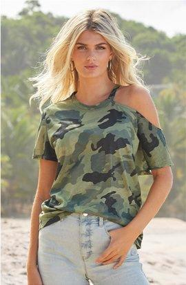 model wearing a camo off-the-shoulder short sleeve top and light wash button fly jeans.